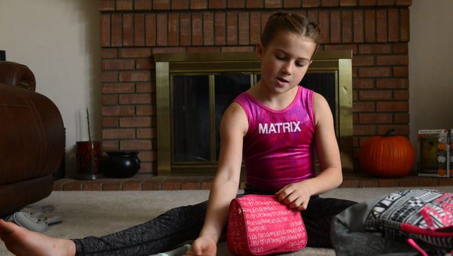 Brooke Blaylock, 10, packs necessities into her daypack, including two EpiPens.