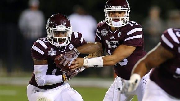 Mississippi State running back Josh Robinson (left) takes a handoff from quarterback Dak Prescott.
