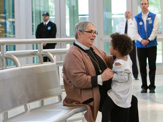 Charlene Frye, 64, of Greece, left, plays with her grand-daughter, Sabrina Smith, 3, at Monday's dedication ceremony for the Downtown Transit Center.