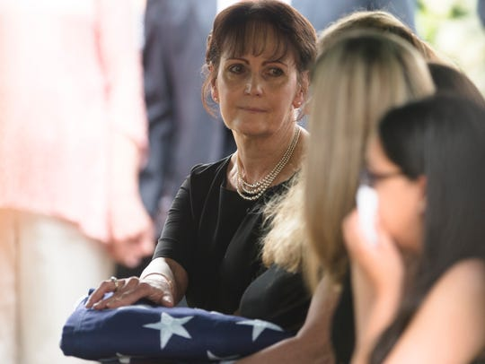 Dana Billingsley holds her late husbands flag during