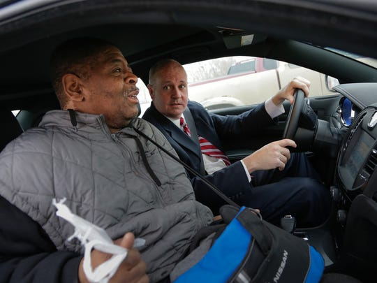 UBS Vice President of Wealth Management Blake Pollock of Rochestor talks with James Robertson, 56, of Detroit, after giving him a ride to work following spotting Robertson walking along Crooks Rd. to his shift at Schain Mold & Engineering in Rochester Hills on Thursday, Jan. 29, 2015.