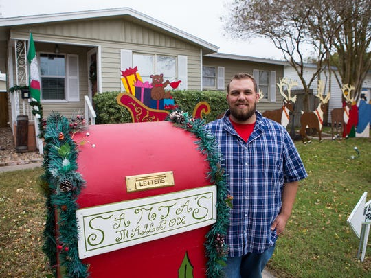 Nickolas Millikan stands next to 'Santa's Mailbox' outside his home at 1206 Belmeade Drive in Corpus Christi, TX.
