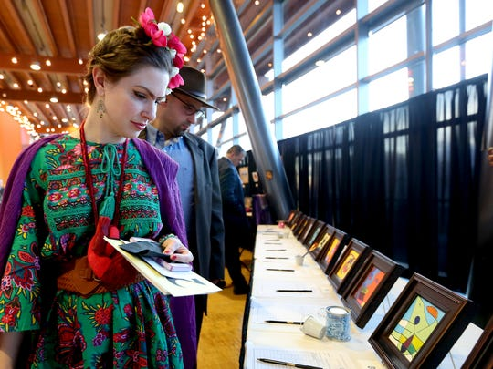 "Erin Gallagher and Aaron Wichman, both 35 and of Salem, dress as Frida Kahlo and Diego Rivera while looking at children's artwork up for auction during the 18th annual Clay Ball at the Salem Convention Center on Saturday, Feb. 25, 2017. The theme for this year's auction and dinner supporting the Salem Art Association was ""Masterpieces"". Attendees were encouraged to dress as their favorite artist or work of art."