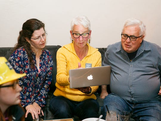 (Left to right) Angela Obery, Judy Martin, and Evan White look at the results of the ballot measure for an $18.6 million bond to upgrade the Salem Public Library on Tuesday, Nov. 7, 2017, in Downtown Salem. Early voting returns showed Measure 24-423 winning with 62.56 percent of the vote in Marion County and 54.46 percent in Polk.