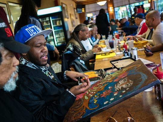 Detroit artist Antonio Taylor talks about one of his art pieces while waiting with other artists to present their work during the Detroit Fine Art Breakfast Club at Noni's Sherwood Grille in Detroit on Monday, May 21, 2018. The meeting helps up-and-coming artists and community members connect with buyers and gallery members during the weekly event.