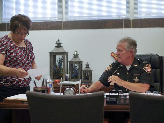 In this Aug. 9, 2017, photo, Lucas County Sheriff John Tharp speaks with his assistant Sandy Heban in his office in Toledo, Ohio. Police and rescue crews say drivers overdosing on heroin and other drugs are driving up the number of car crashes. Tharp says drivers in his county overdose on opioids so powerful it requires multiple doses of opiate antidote naloxone in order to revive them. (AP Photo/Dake Kang)