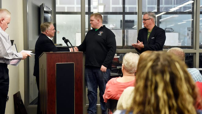 York County 911 dispatcher Sam Myers shakes hands with York County Commissioner Doug Hoke after being recognized as 2015 Telecommunicator of the Year Friday, April 15, 2016, at the York County 911 Center. The York County Department of Emergency Services annually celebrates its employees for a week in April, culminating in an awards ceremony.