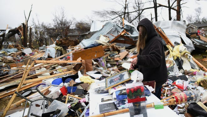 Rhonda Cooper salvages items Wednesday, Nov. 30, 2016, from the remains of a mobile home where two people were killed on Stump Street in Polk County, Tenn., after a tornado swept through the area early Wednesday. A suspected tornado was responsible for the death of a husband and wife in southern Tennessee's Polk County, while an unknown number of others were injured, said Tennessee Emergency Management Agency spokesman Dean Flener. (Angela Lewis/Chattanooga Times Free Press via AP)