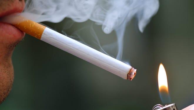 A man lights a cigarette with a lighter.