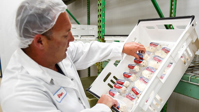 Glen Wood, general manager of Stickney Hill Dairy goat cheese production facility shows some of the different flavors produced including cranberry cinnamon Wednesday, June 14, in Rockville.
