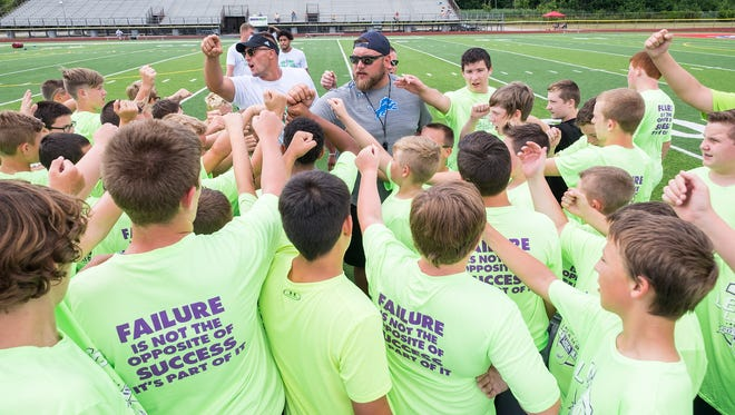 Former Detroit Lions offensive lineman and St. Clair graduate Tim Lelito, center, gets kids hyped up before a session of the Lelito Legacy football camp Wednesday, July 18, 2018, at East China Stadium.