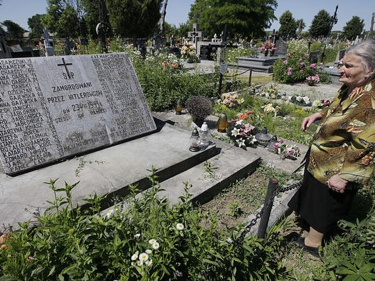 In this June 19, 2013, file photo, a woman stands near a mass grave and a monument in the village of Chlaniow, Poland, that holds the bodies of Poles killed in a 1944 attack on the village by the Nazi SS-led Ukrainian Self Defense Legion.
