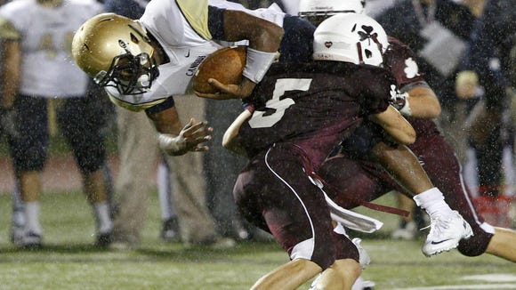 Aquinas's Donato Clemente, right, tackles Canisius's Qadree Ollison in the open field during football action between the Canisius (Buffalo) Crusaders and the Aquinas Lil Irish in Rochester Friday evening, September 13, 2013.