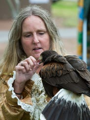 Sheila Lang, with Hawk Quest, holds a Harris Hawk during