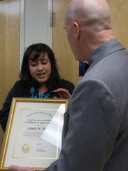 Linda Perez, receives an award from Michael Amaral,