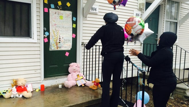 Toni Williams, 28, left, and Natasha Bell, 30, leave balloons Wednesday morning at the town house in the Martin Luther King Apartments where two children were found dead in a freezer on Tuesday. The women said they didn't know the family very well but feel sorry for the children.