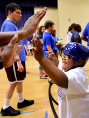 Jovan gets high fives from MTSU football players after running with a football on Thursday, June 25, 2015, during Camp Ability.