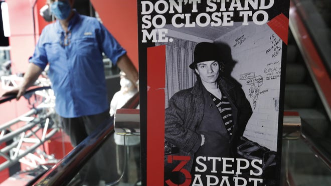 A social distancing sign rests near an escalator at the Rock and Roll Hall of Fame in June in Cleveland.