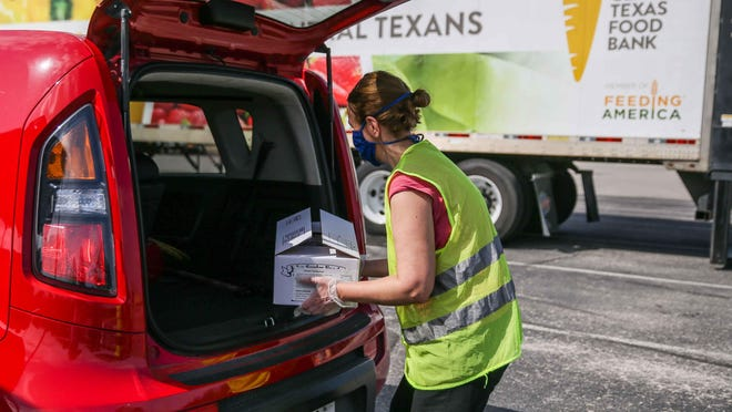 Kasia Barenska delivers emergency food kits distributes by Central Texas Food Bank at the Tony Burger Stadium in Austin  in July.