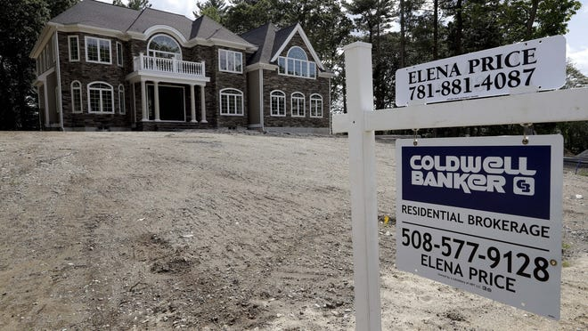 In this September 2019 file photo a sign rests in front of a newly constructed home in Westwood. The Warren Group reported Wednesday that Massachusetts single-family home sales rebounded in July on a year-over-year basis following three consecutive months of double-digit declines.
