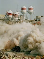 Water towers begin to fall into rubble during the implosion