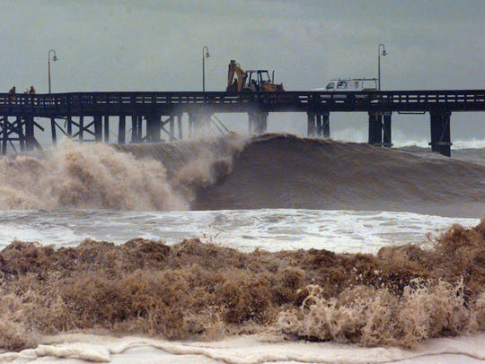 Work crews attempt to repair a pier damaged by waves