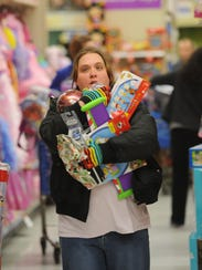 Toys R Us announced last week it would be liquidating its U.S. business. The impending closure of the Williston store will deepen a retail void for parents shopping for children's gear, clothing and toys, say some. In this photo a shopper has an armload during Black Friday shopping in 2010 in Illinois.