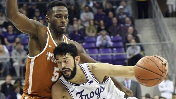 Texas's Kendal Yancy, left, tries to block TCU's Alex Robinson as he drives to the basket in the first half of an NCAA college basketball game Saturday Feb. 4, 2017, in Fort Worth, Texas. TCU went on to win 78-63.