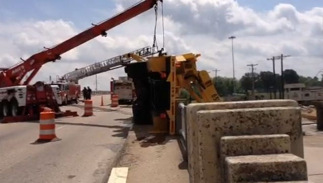 Crews try to right a crane that flipped over and pinned the operator under it. The unidentified worker reportedly suffered only minor injuries.