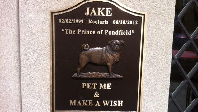 The bronze plaque for Jake attracts wish-makers at the Bronxville art gallery.