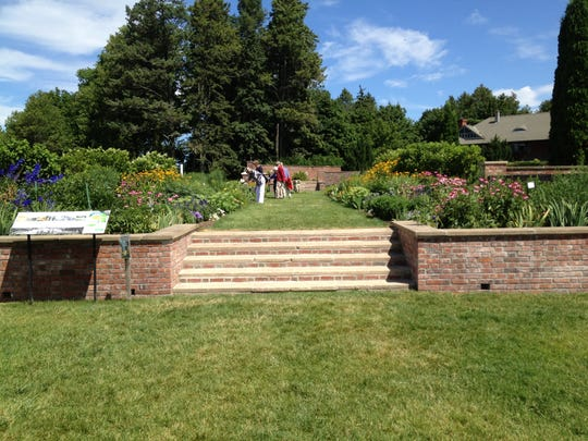 Visitors stop to smell the flowers in the formal gardens at Shelburne Farms in July 2014.
