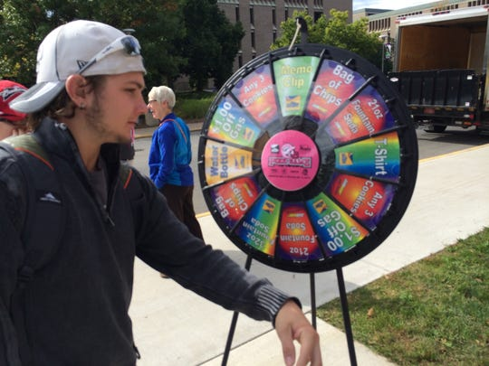 Harry Kasprzyk, a sophomore at the University of Wisconsin-Stevens Point, spins a wheel to win a prize from Team Schierl Companies as part of homecoming activities on Wednesday in front of the Health Enhancement Center.