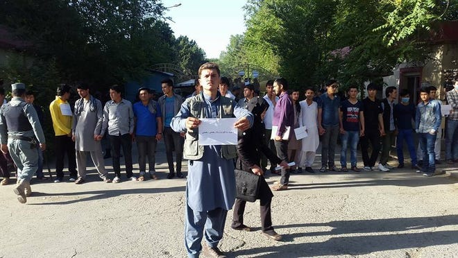"""Students atthe entrance of Kabul University on June 6, 2016. The sign reads, """"We want vacation"""" in Dari, the language spoken in Afghanistan."""