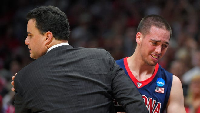 Arizona guard T.J. McConnell hugs head coach Sean Miller as McConnell leaves the game late in the second half of a college basketball regional final against Wisconsin in the NCAA Tournament, Saturday, March 28, 2015, in Los Angeles. Wisconsin beat Arizona 85-78 to advance to the Final Four.