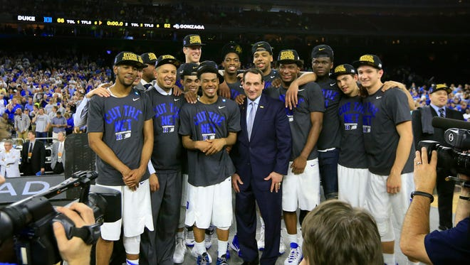 Duke Blue Devils head coach Mike Krzyzewski stands with his players on the podium after defeating the Gonzaga Bulldogs in the finals of the south regional of the 2015 NCAA Tournament at NRG Stadium.