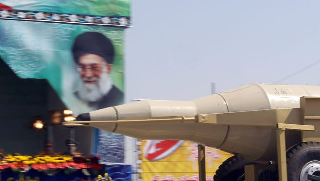 A military truck carries a Sejil medium-range missile past a large portrait of Iran's supreme leader, Ayatollah Ali Khamenei, during an annual military parade.