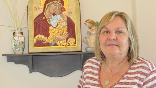 Fleury with a sample of the religious images she paints at her Union home.