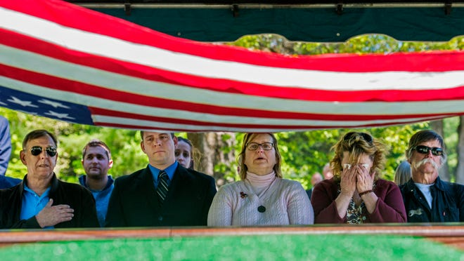 Members of John Metruk's family watch as the flag is lifted off the Korean War veteran's casket during his burial at Mountain View Cemetery in Essex on Thursday. From left: Metruk's son John S. Metruk; grandson Joe Cogley; daughters Nancy Gianni and Susan Cogley; and son Paul Metruk. The family received Metruk's Purple Heart during the ceremony.