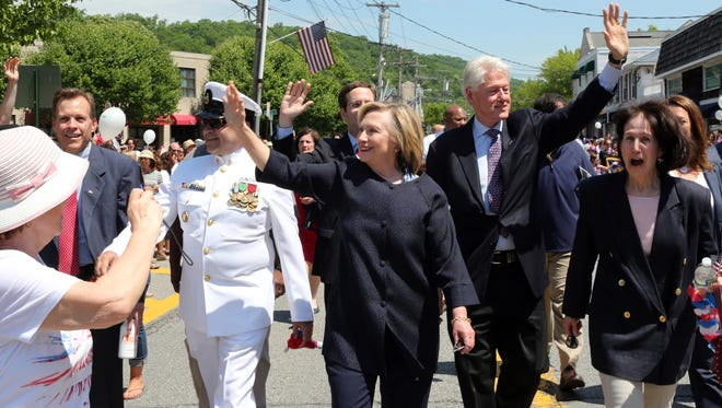 Presidential candidate Hillary Clinton and former President Bill Clinton march in New Castle's Memorial Day parade, May 25, 2015.