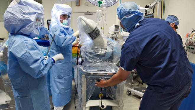 Dr. Joseph Nessler, second from left, is assisted by a drill on a robotic arm May 21 as he prepares for a total hip replacement at the St. Cloud Surgical Center. Nessler was using the new surgeon-controlled RIO robotic arm technology for precise and accurate alignment when placing implants.