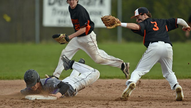 West De Pere shortstop Matt Bald (3) tries to tag out Denmark's Riley Pelischek during a play at second base in Tuesday's baseball game in Denmark.