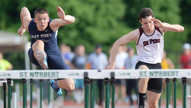 Bay Port's Zachary Lorbeck, left, sails over the 110-meter hurdles against De Pere's Christian Albers during the WIAA Track and Field Sectional Meet at Schneider Stadium Friday.
