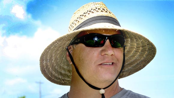 Blackman's new head  coach David Watson tries to stay cool and sun freee under his big straw hat as Blackman competes in the during the 7-on-7 Bojangles Passing Tournament at Riverdale, on Thursday, July 9, 2015.