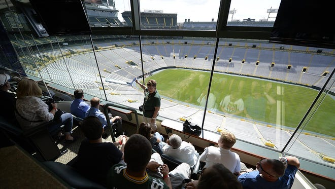 Fans listen to tour guide Candy Conard as she talks about the history of the stadium while visiting a private suite during a Lambeau Field stadium tour.