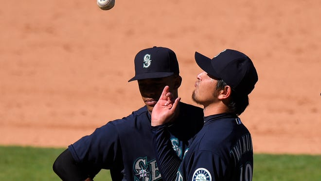 Seattle Mariners starting pitcher Hisashi Iwakuma, of Japan, tosses the ball in the air as he waits to be taken out of the baseball game as shortstop Ketel Marte watches during the eighth inning against the Los Angeles Angels, Sunday, Sept. 27, 2015, in Anaheim, Calif.