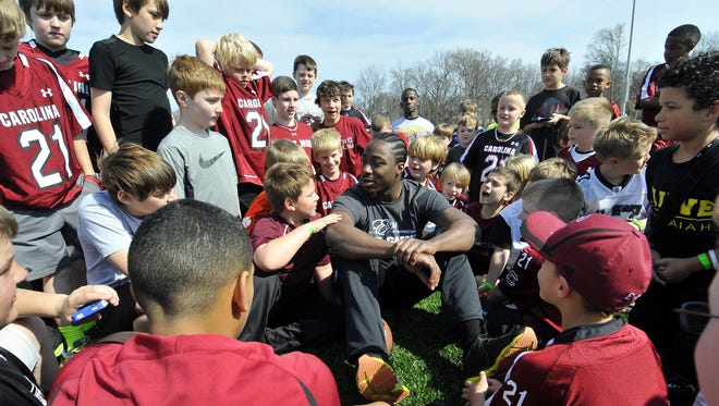 Marcus Lattimore, surrounded by kids wearing replicas of his USC jersey at a 2013 MVP Football Camp at the Kroc Center, will be the keynote speaker at the Nov. 3 fundraiser dinner for Generations Group Homes. Marcus Lattimore speaks to a group of kids at the MVP Football Camp at the Kroc Center in Greenville on Saturday, March 16, 2013.
