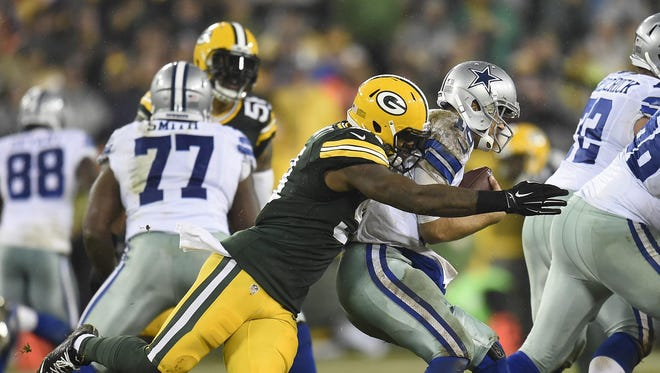 Packers linebacker Jayrone Elliott (91) sacks Cowboys quarterback Matt Cassel (16) at Lambeau Field.