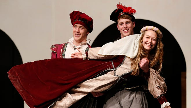 """St. Mary's Springs' students Hortensio (Eric Reid) and Lucentio (Aaron Schmitz) hold Bianca (Anja Ozols) during their rehearsal of """"Kiss Me, Kate."""""""