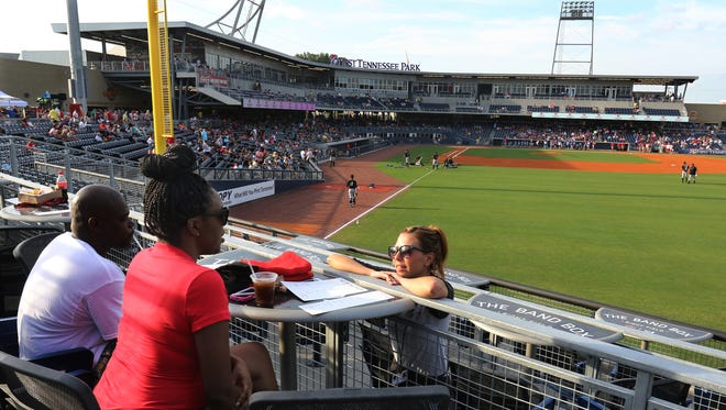Server Kaley Parks, right, takes an order from Shelia McGee, center, and Willie C. Swanson Jr. in The Band Box restaurant and bar at  First Tennessee Park last summer. The 2016 season has lots of promotional deals to keep fans cheering.
