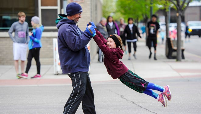 Mark Fitzgerald from Conrad, swings his granddaughter, Bryn Fitzgerald, 6, in the street before the 37th Annual Ice Breaker Sunday, April 24, 2016.